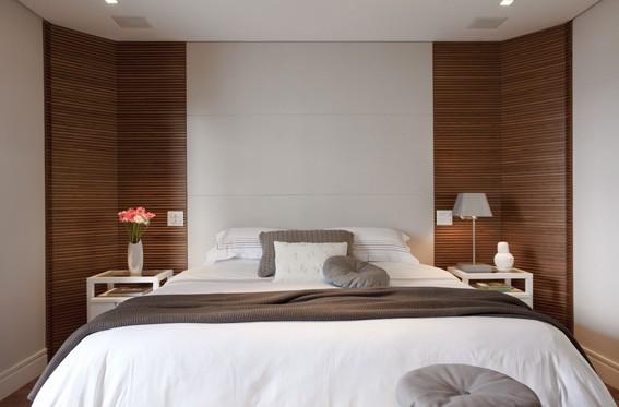 Cabeceira de madeira branca com madeira ripada na suite