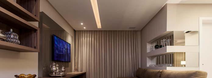 Forro de gesso com rasgo de luz e parede com nichos embutidos na sala