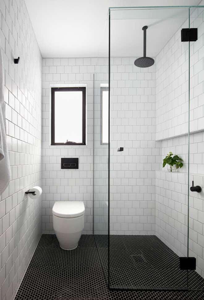 banheiro com revestimento tijolinho branco e piso preto
