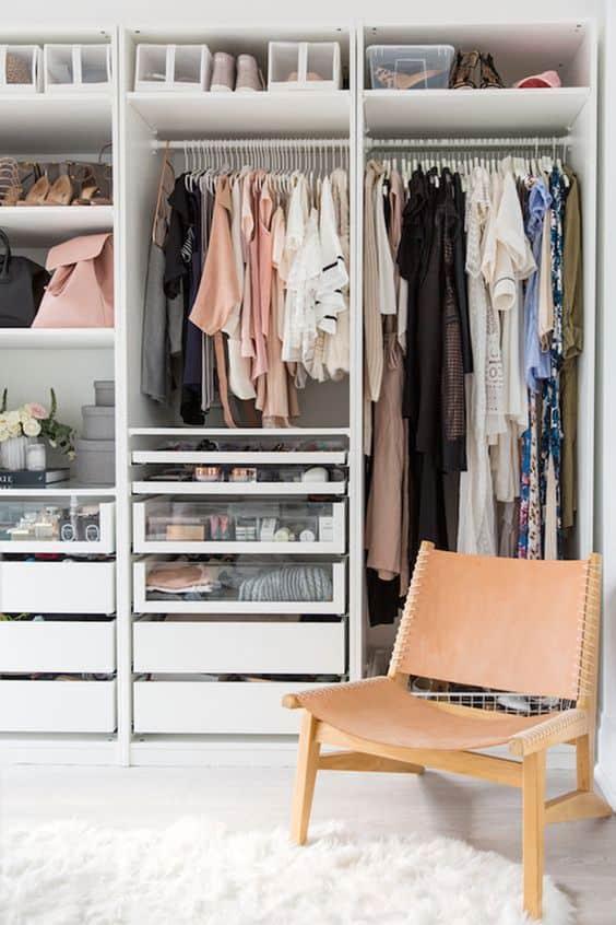 Closet organizado com roupas penduradas, gavetas e prateleiras