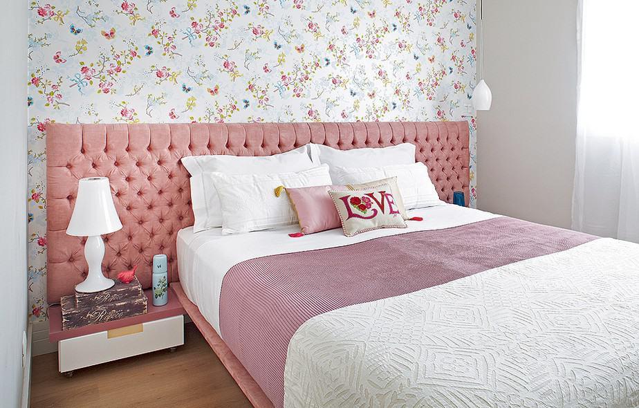 Cabeceira capitonet rosa em quarto pequeno com papel de parede