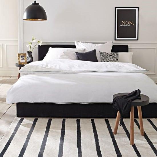 Ideia simples para decorar um quarto preto e branco com tapete listrado e cama preta