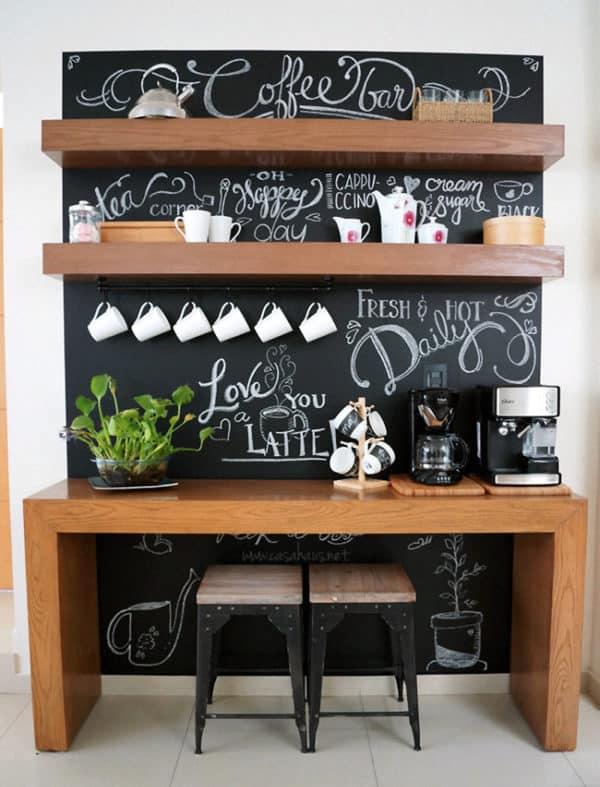 Bancada moderna para café com parede de lousa e banquetas de ferro