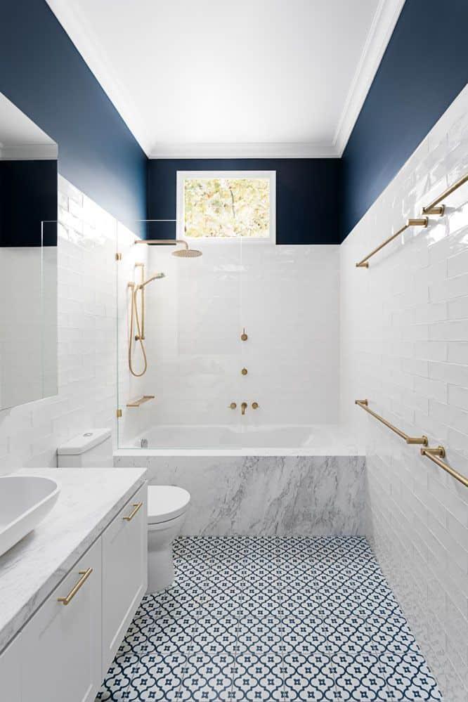 Banheiro branco com parede pintada de azul e piso geométrico