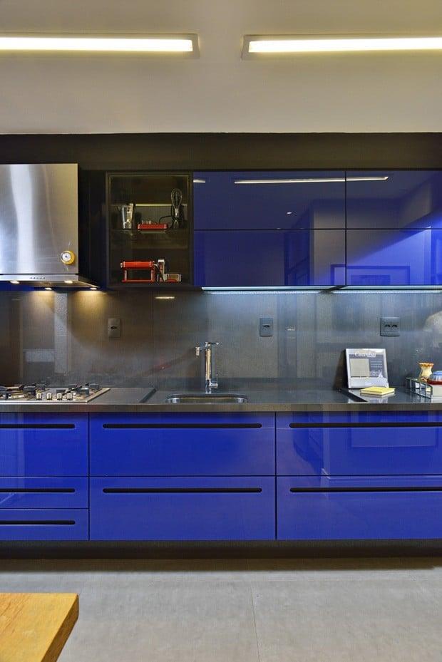 Móveis azul escuro brilhosos na cozinha com tampo cinza