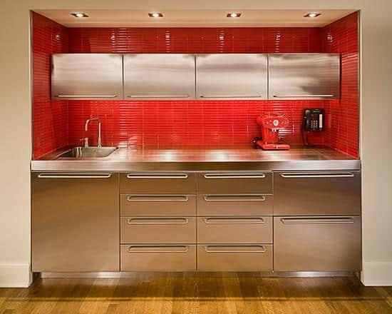 Pastilhas vermelhas na cozinha de inox