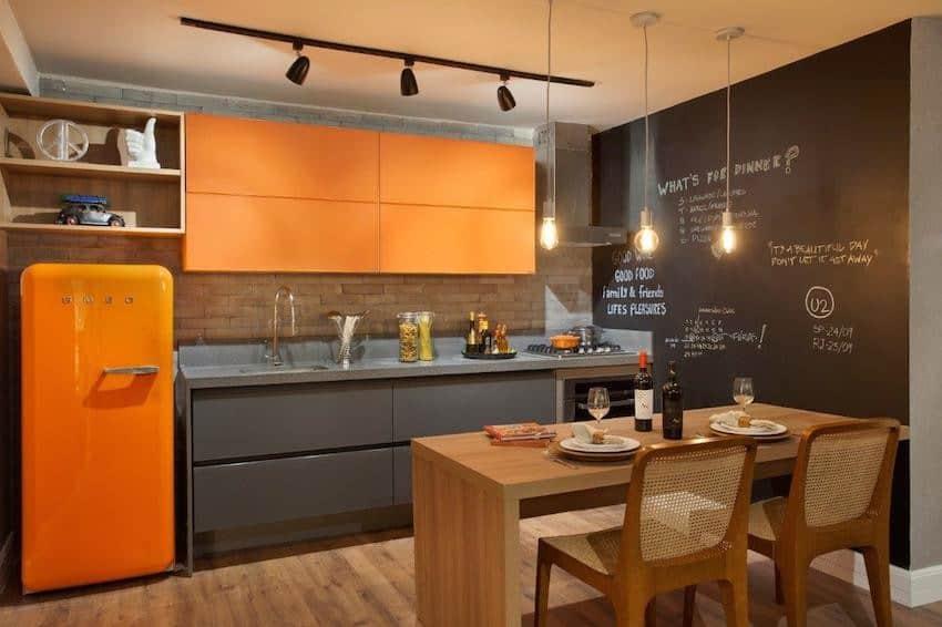 Cozinha moderna laranja, cinza e amadeirado com parede de lousa