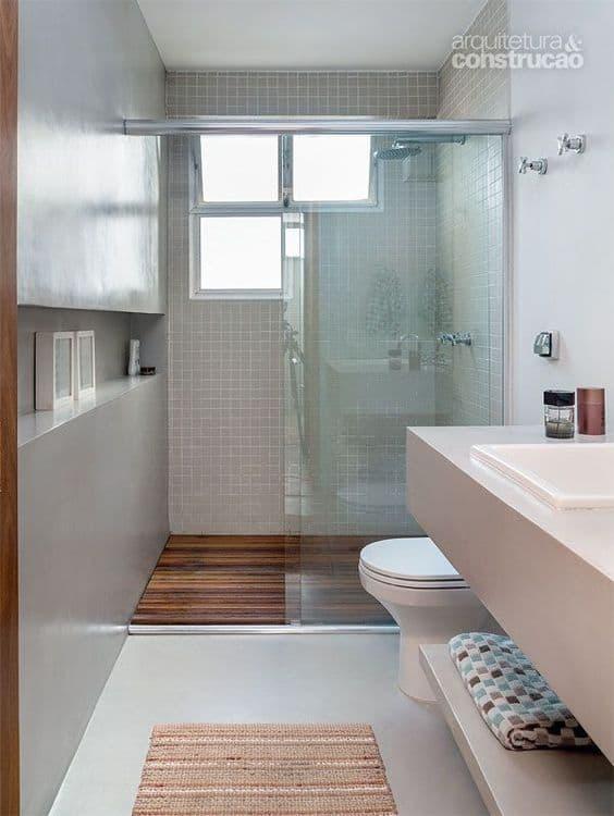 Banheiro branco com parede de cimento queimado e box com piso de deck