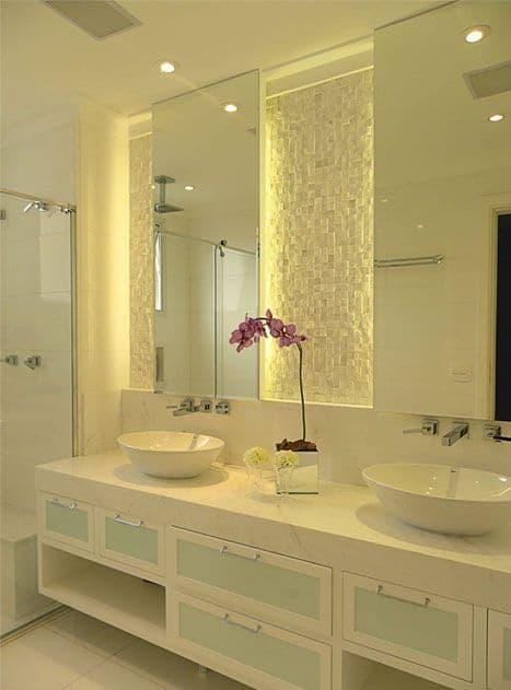 revestimento de mosaico de pedra e a iluminação atrás dos espelhos
