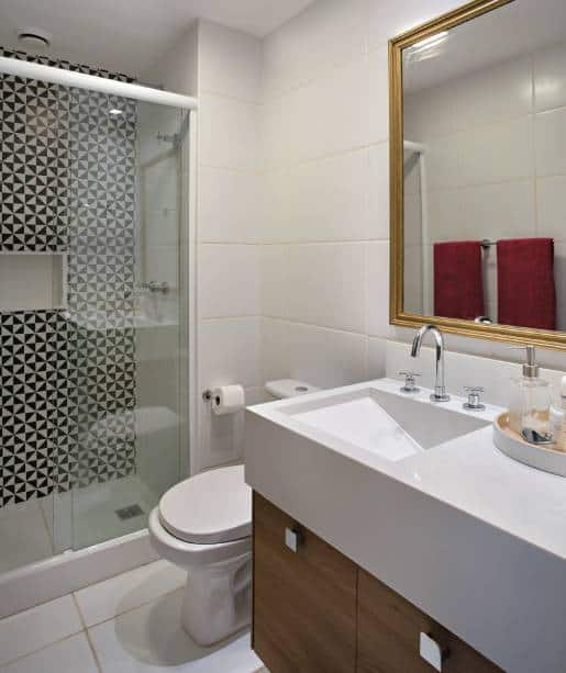 Banheiro pequeno com detalhe de revestimento preto e branco no box