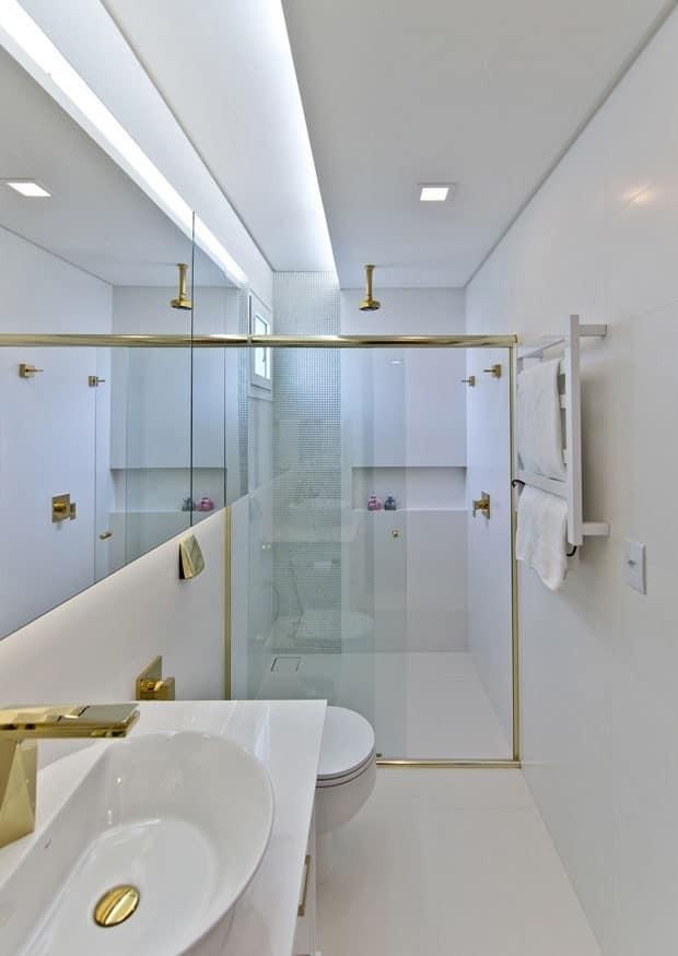 Banheiro pequeno branco com acessórios dourados e iluminação