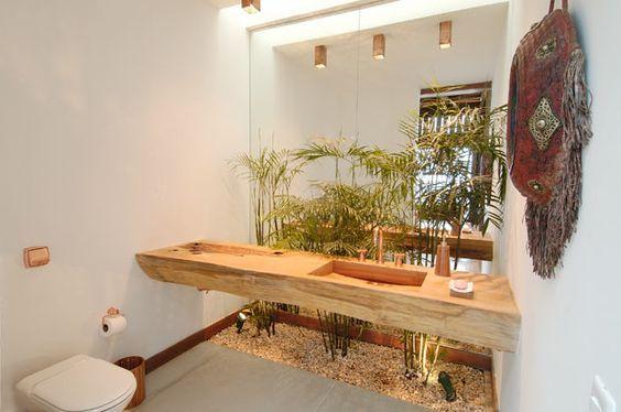 Tampo de madeira rústica e decoração com plantas no banheiro