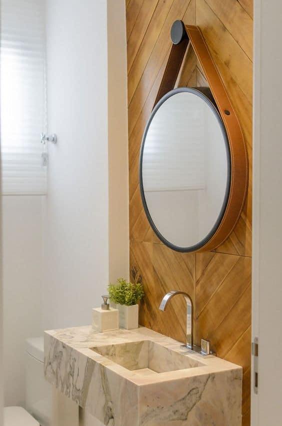 Espelho com alça de couro e parede de madeira no lavabo pequeno