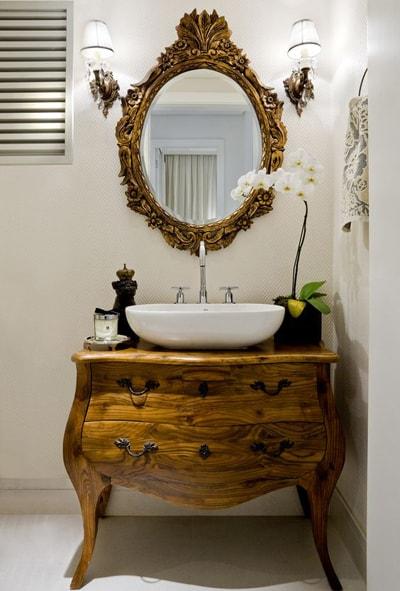 Decoração clássica com espelho de moldura dourada e balcão de cômoda antiga