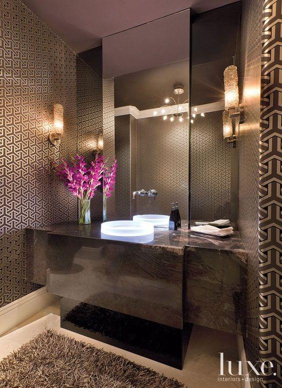 Lavabo elegante com papel de parede estampado e arandelas de cristal