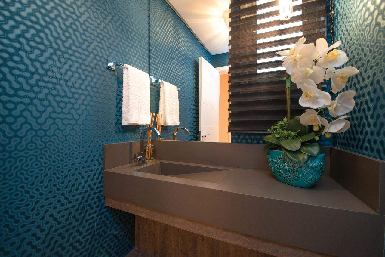 Lavabo decorado com papel de parede azul e tampo marrom