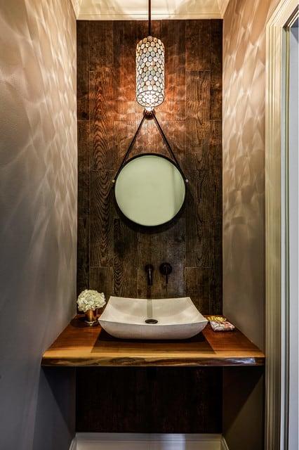 Decoração de lavabo pequeno com espelho com alça e parede revestida de porcelanato que imita madeira