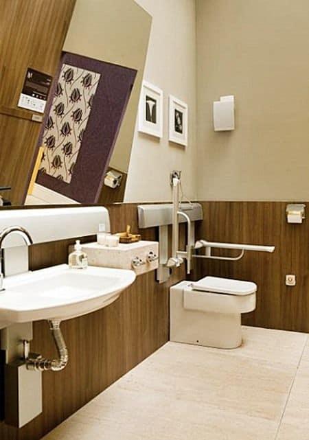Acessibilidade no banheiro com espelho inclinado e barras