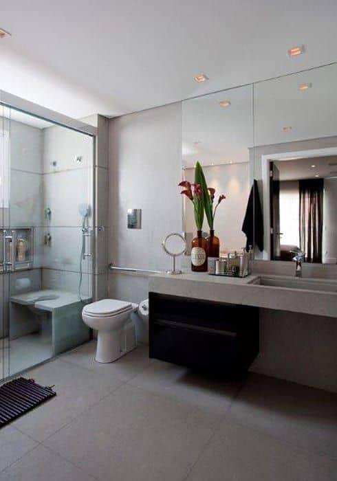 Banheiro residencial com acessibilidade e banco no box
