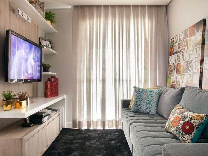 Sala de de apartamento decorada com tons claros e detalhes coloridos