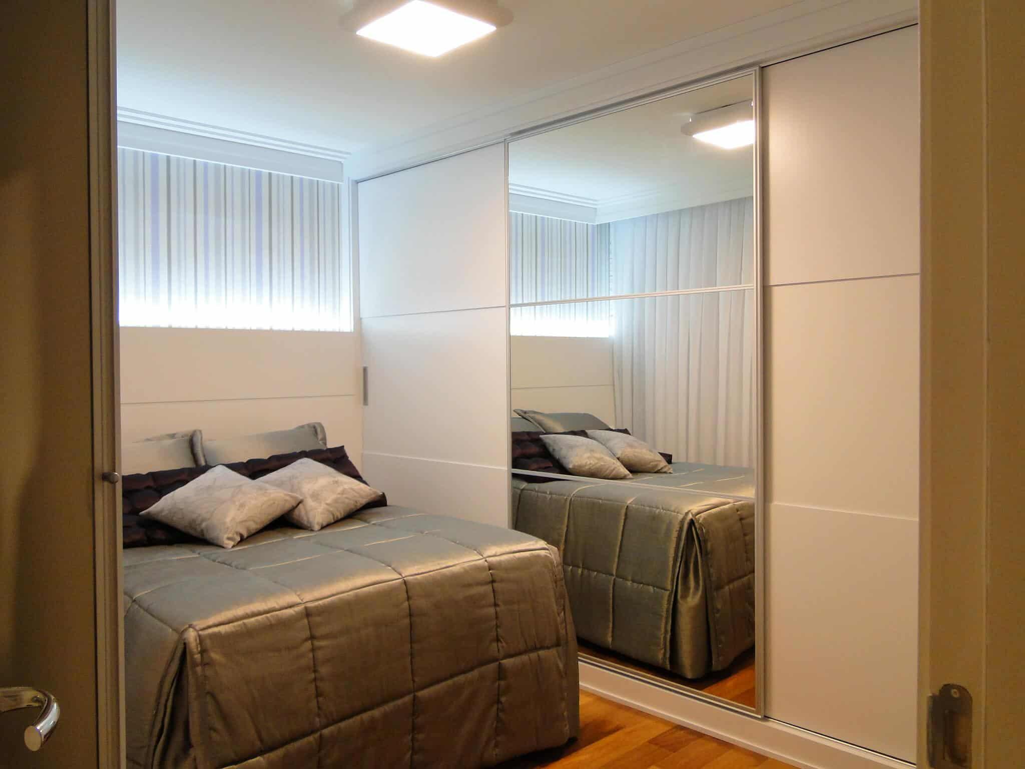Quarto de casal com armários brancos e papel de parede