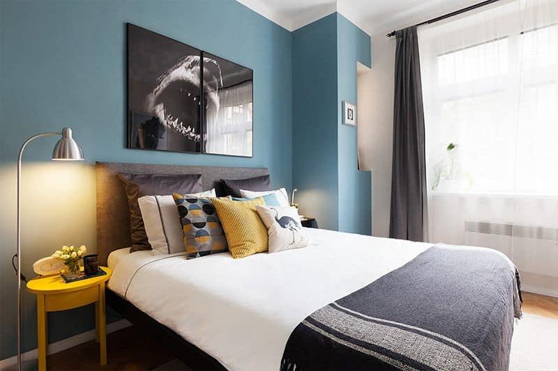 Dormitório com parede azul, decoração moderna e colorida