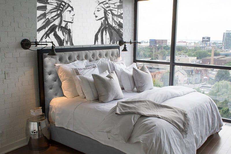 Quartos com tijolos a vista e painel moderno, com cabeceira elegante estofada