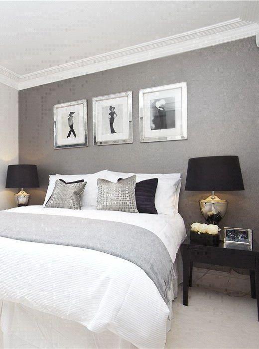 Dormitório elegante, com quadros e parede pintada de cinza