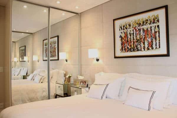 . Dormitório pequeno com decoração bonita, cabeceira estofada até o teto e quadro na cabeceira