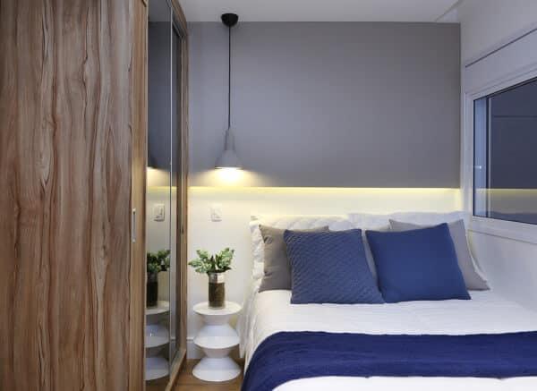 Quarto pequeno com decoração moderna e simples. Pendente na lateral da cama e cama no canto.