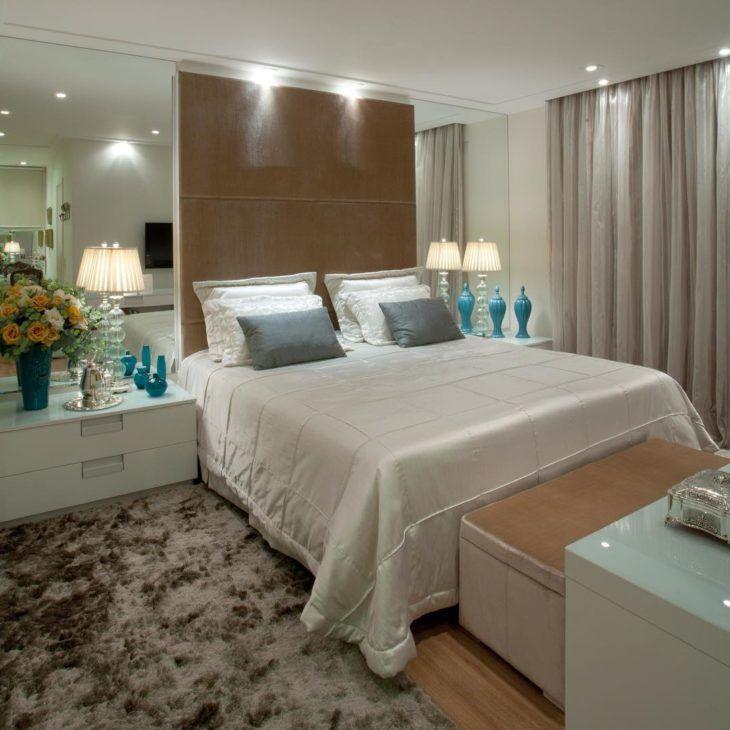 Decoração elegante com cama estofada, abajur elegantes e espelhos nas laterais da cama
