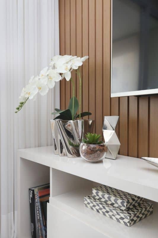 Ideia de vaso com orquídea sobre o rack da TV, perto da janela.