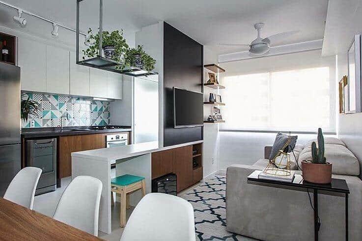 Sala simples integrada com a cozinha, com prateleiras e sofá grande