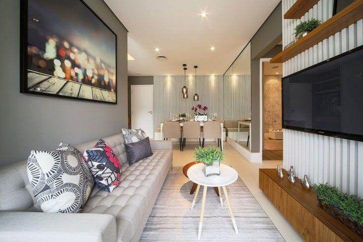 Sala moderna em apartamento pequeno, com espelho no jantar e painel para TV ripado