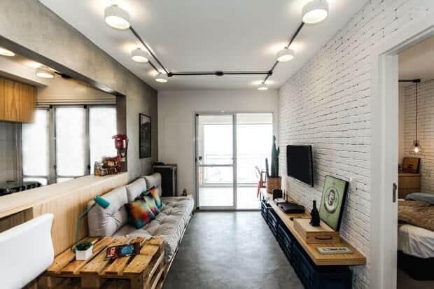 Decoração simples na sala com sofá de pallet e parede de cimento queimado