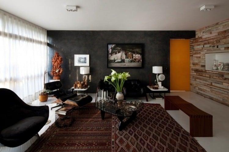 sala com parede preta e sofas com decoracao laranja