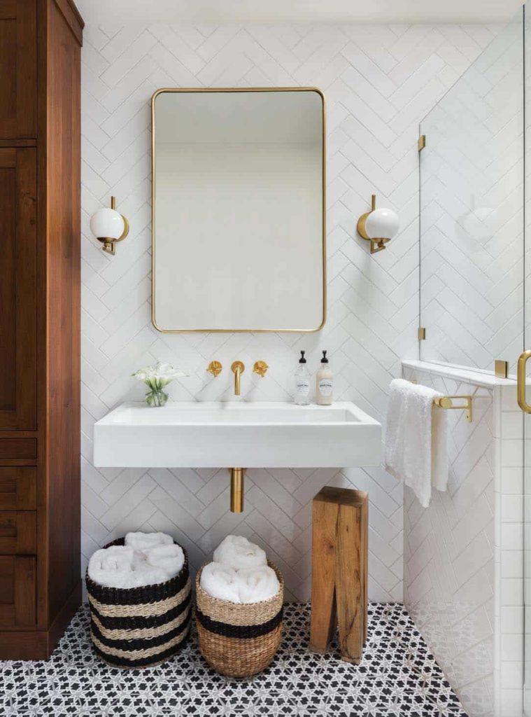 Banheiro moderno com espelho com metais dourados e cuba de parede