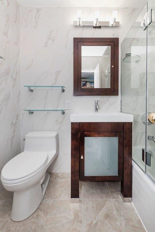 Banheiro claro com móvel de madeira