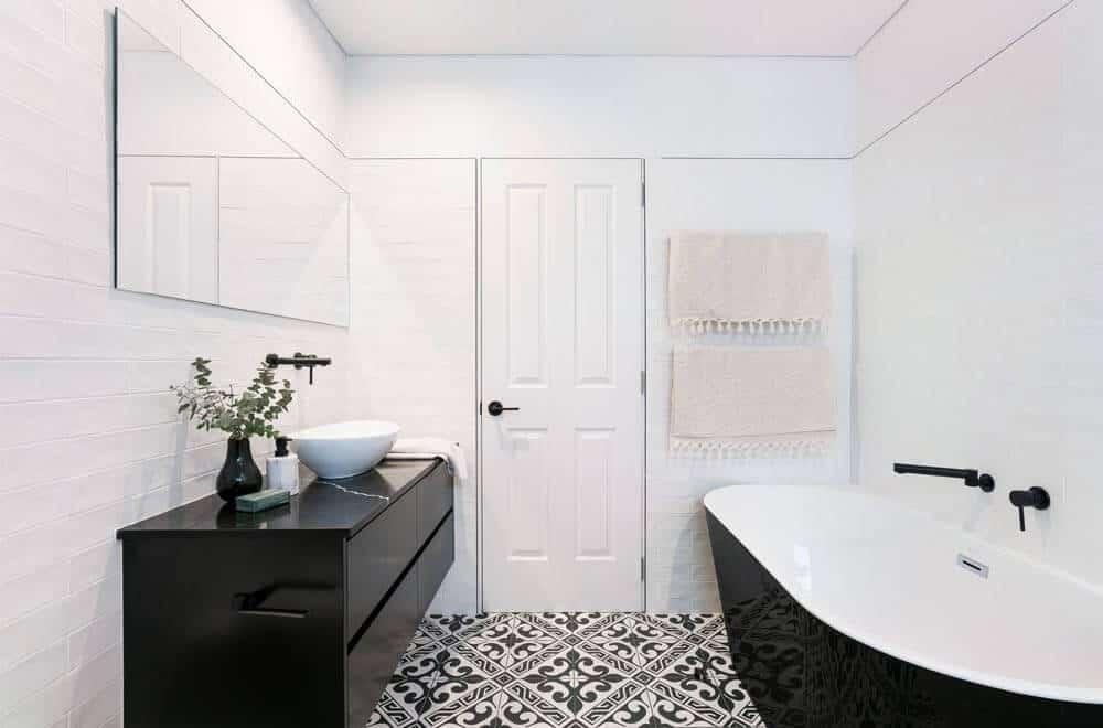 Paredes brancas com móveis pretos no banheiro